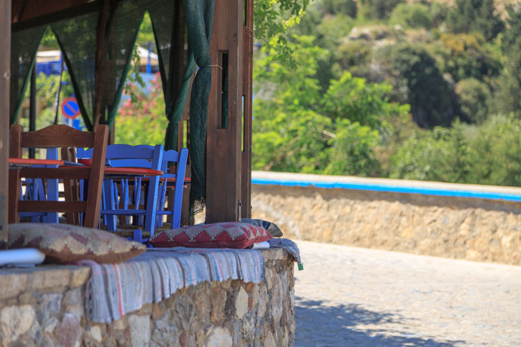 Tables And Chairs At Cafe By Road During Sunny Day