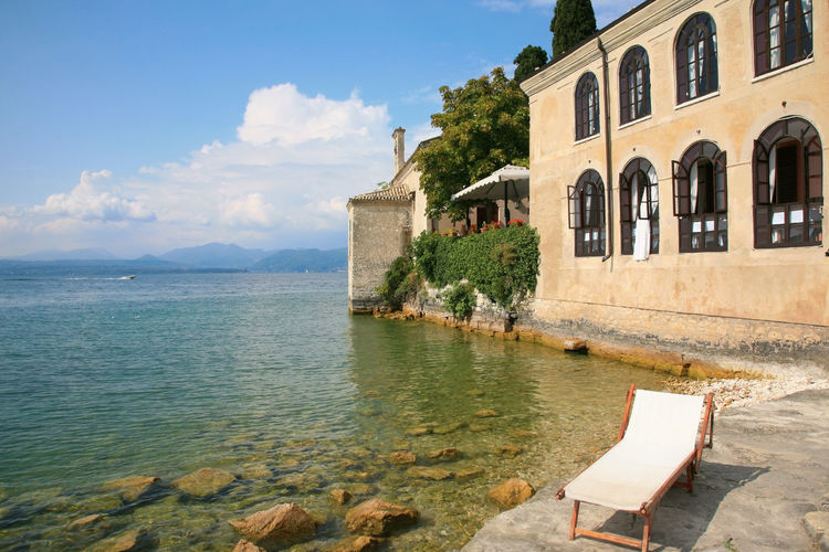 Beach chair at Lake Garda in Italy Architecture Beach Chair Beauty In Nature Building Exterior Built Structure Cloud - Sky Day Italian Italy Lake Lake Garda Nature No People Outdoors Sky Sunbath Tourism Tranquility Travel Tree Water