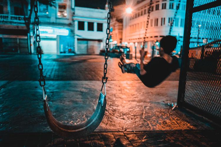 Rear view of boy swinging at night