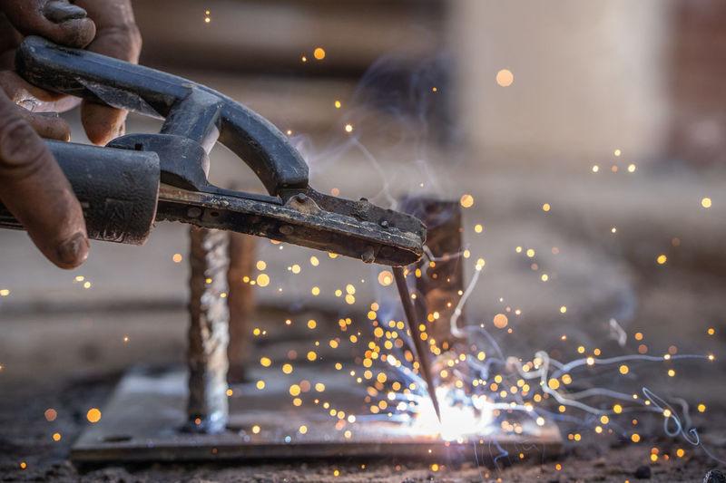 Cropped hands of worker welding metal in workshop