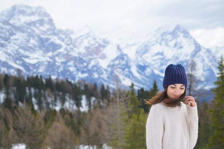 Young woman in warm clothing standing against snowcapped mountain