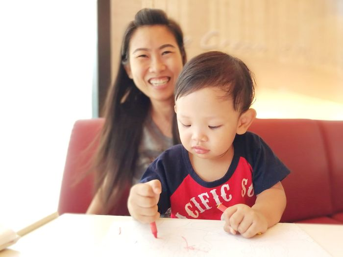 Boy drawing on paper while sitting with mother at home