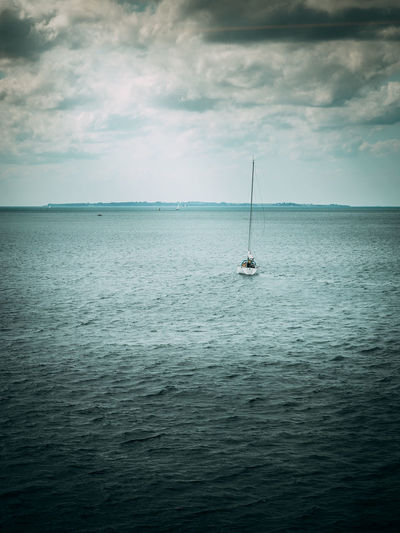 Sailboat sailing on sea against sky