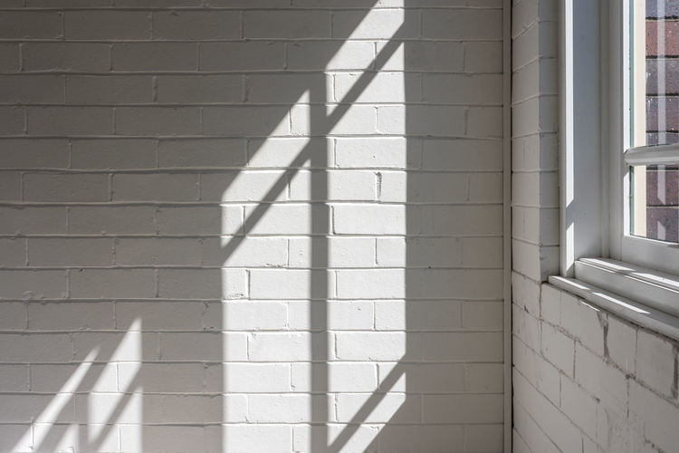 Sunlight and hard shadows from window against white brick wall in corner of room Background Brick Calm Copy Space Corner Frame Home Imperfect  Indoors  Interiors Light Minimal Room Rustic Shadows Sill Simplicity Sun Sunlight Urban Wall White Window Shadow Wall - Building Feature Built Structure Day No People Brick Wall White Color Focus On Shadow Pattern