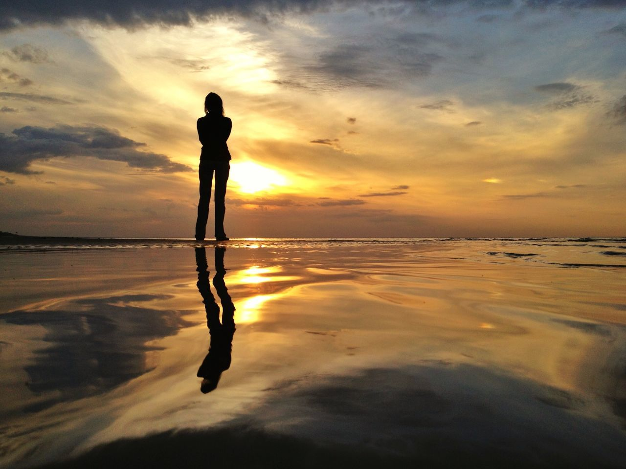 Reflection of silhouette woman on beach against sky during sunset