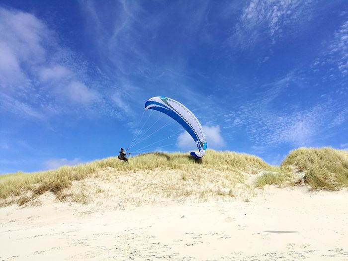 Side view of person paragliding at beach against blue sky during sunny day