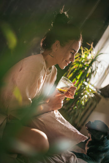 Midsection of person holding drink sitting outdoors