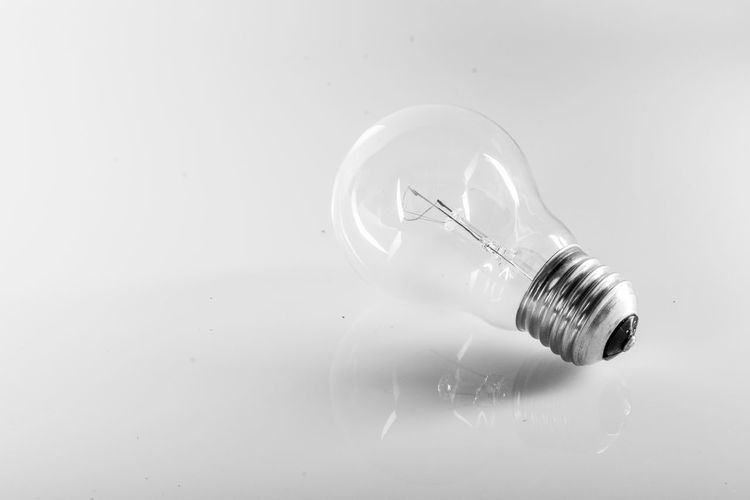 Close-up of light bulb over white background