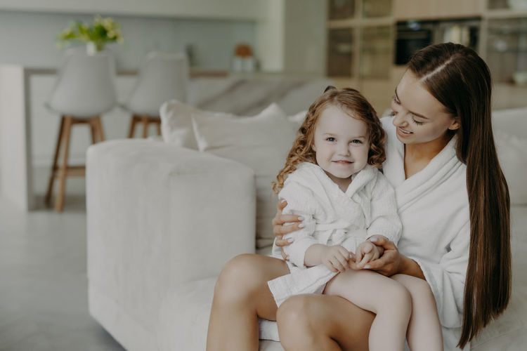 Smiling mother with daughter sitting on sofa in bathrobe