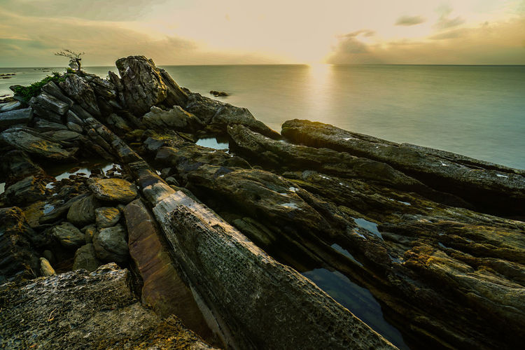 Stack of rocks by sea against sky during sunset