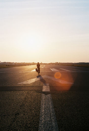 Symbol Road Transportation Sunlight One Person Sunset Nature Full Length Riding Ride Sky Sport Shadow Marking Real People Mode Of Transportation Bicycle Road Marking City Outdoors Lens Flare Tempelhofer Feld Analogue Photography Analog 35mm