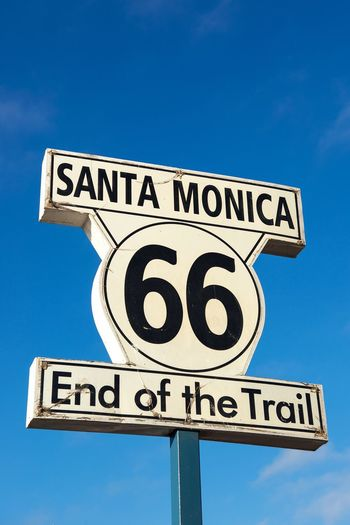 End Of The Trail End Route 66 Santa Monica California Pier Guidance Road Sign Communication Text Directional Sign Copy Space Direction Blue Arrow Symbol Marker 66 Motherroad Low Angle View Outdoors No People Clear Sky Street Name Sign Sky Close-up California Dreamin