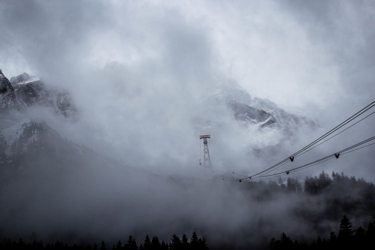 Fog Sky Cloud - Sky Mountain Beauty In Nature Nature No People Tranquil Scene Scenics - Nature Tree Tranquility Environment Low Angle View Day Cable Plant Cold Temperature Connection Non-urban Scene Outdoors Mountain Peak Pollution Power Supply