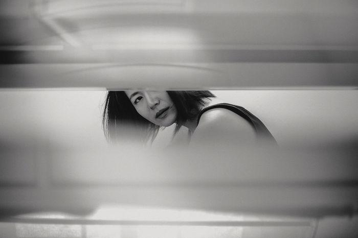 Portrait of mid adult woman sitting in bathroom seen through window blinds