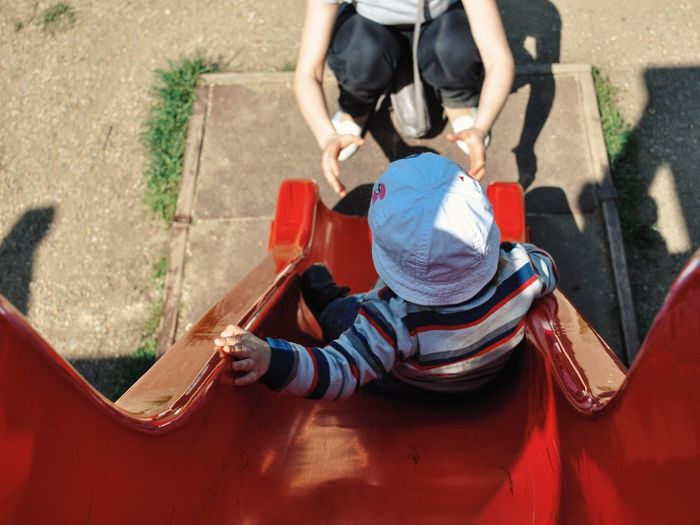 High Angle View Of Child Sliding Towards Mother In Playground