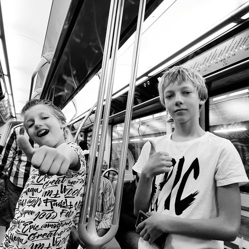Portrait of male friends gesturing thumbs up in subway train