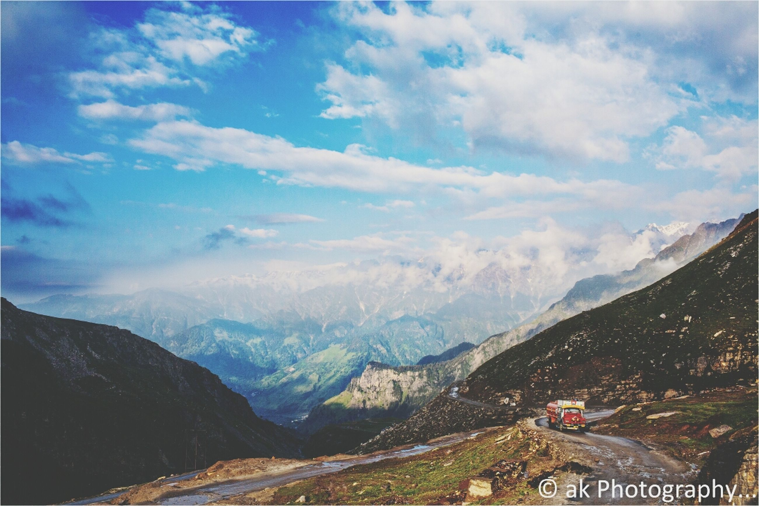 mountain, sky, mountain range, scenics, landscape, tranquil scene, beauty in nature, tranquility, cloud - sky, nature, cloud, non-urban scene, transportation, high angle view, cloudy, road, idyllic, remote, day, outdoors