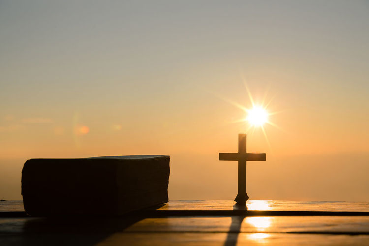 Resurrection of Jesus Christ concept: Silhouette cross with bible on hill sunrise background Sky Sun Sunset Orange Color Religion Spirituality Water Sunlight Belief Nature Cross Lens Flare Copy Space Sunbeam Silhouette Beauty In Nature Sea No People Outdoors Religious Equipment