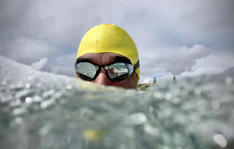 Portrait of man wearing sunglasses swimming in sea