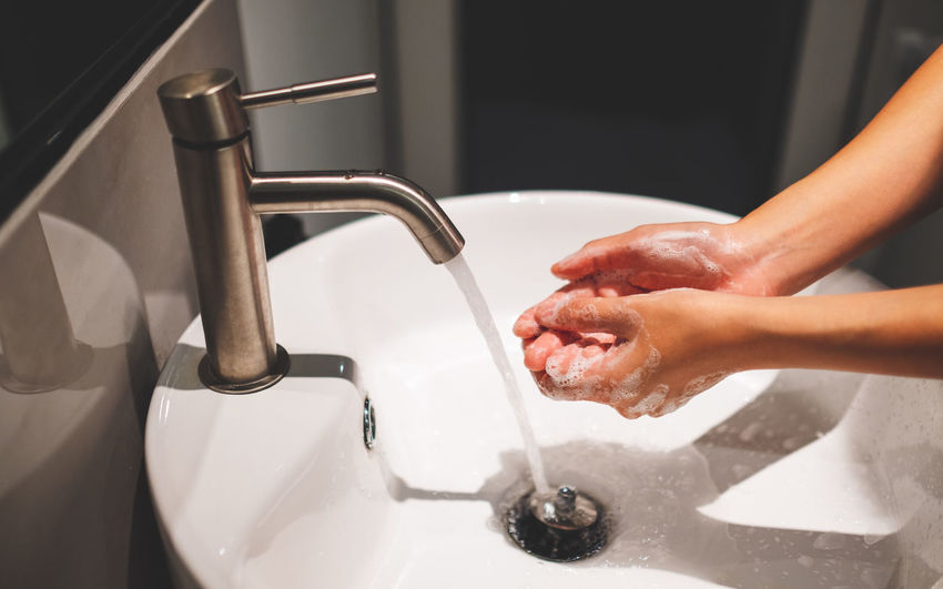 Woman washing hands in sink at home