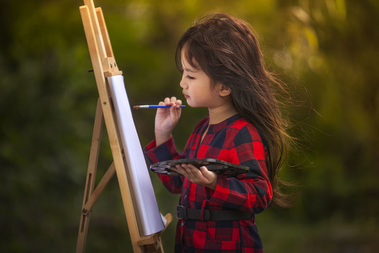 Girl painting on paper over easel at outdoors