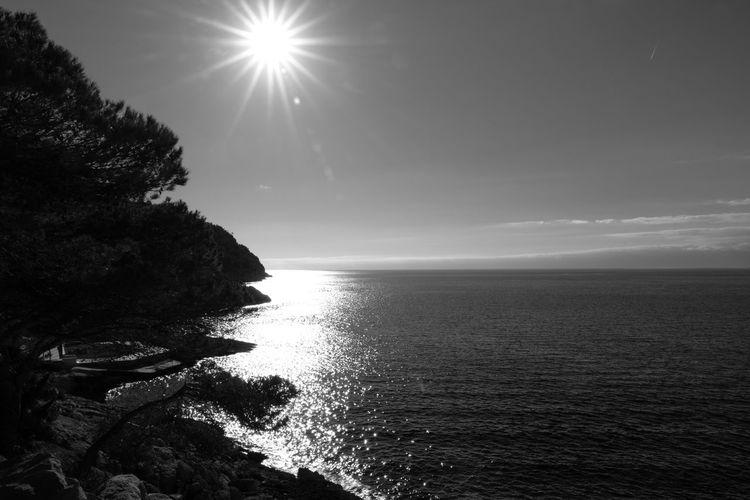 Scenic view of sea against bright sun