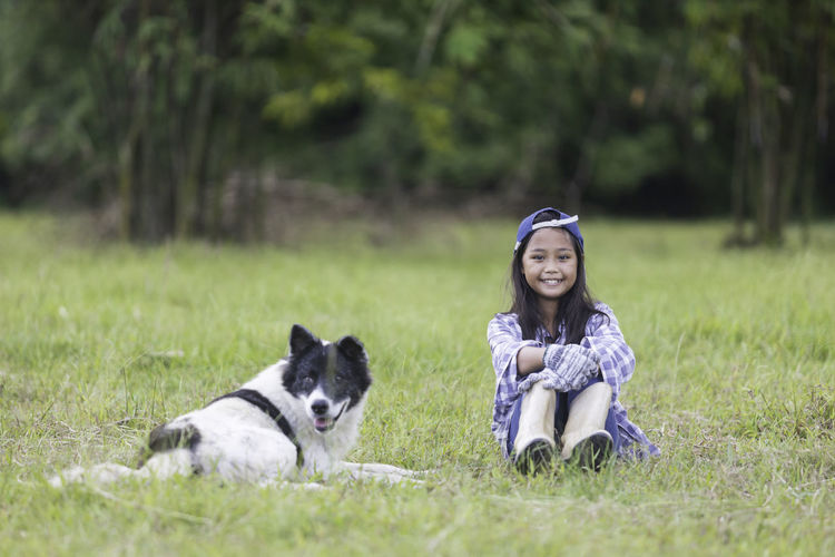 Portrait of smiling girl sitting by dog at park