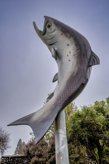 Low angle view of animal sculpture against sky