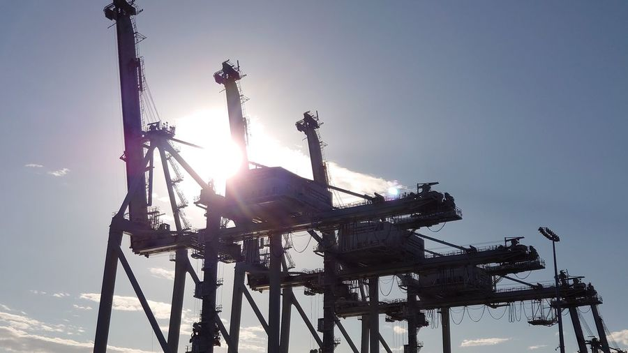 Low angle view of silhouette crane against clear sky