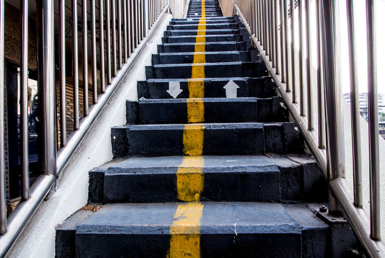 Yellow line and direction arrow painted on concrete stair of overpass