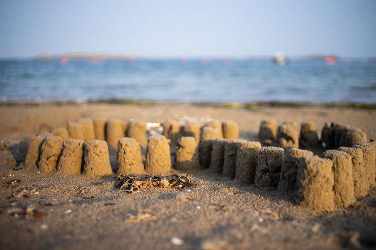 Stone wall on beach against sky