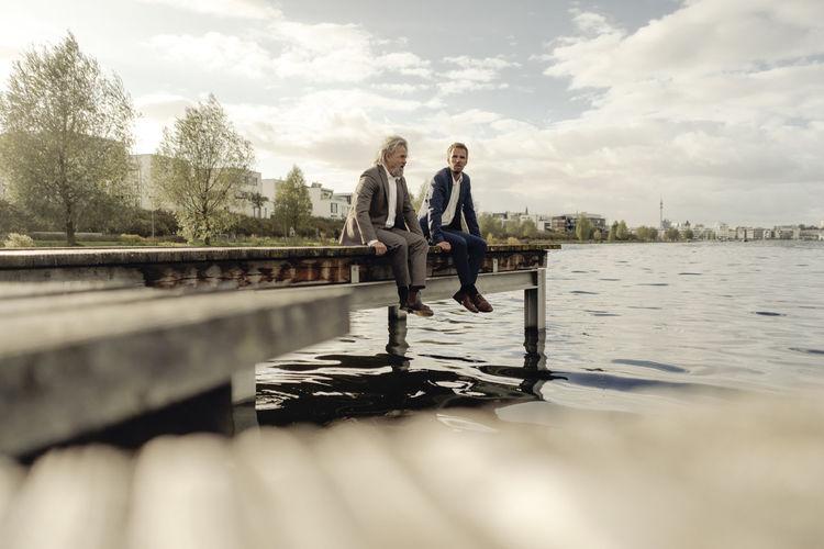 People standing on lake against sky