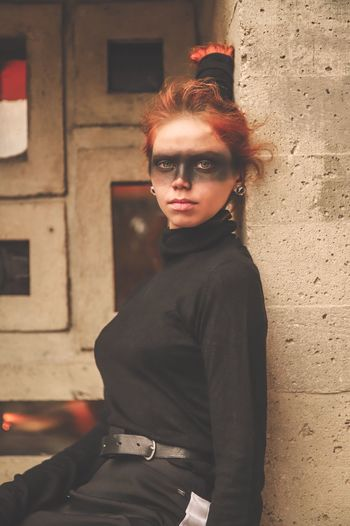 Portrait of woman with face paint standing against wall