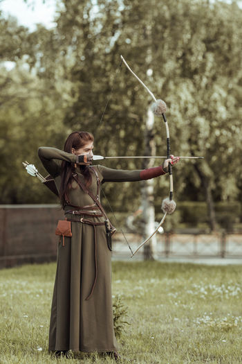 Full length of archer holding bow and arrow standing on field