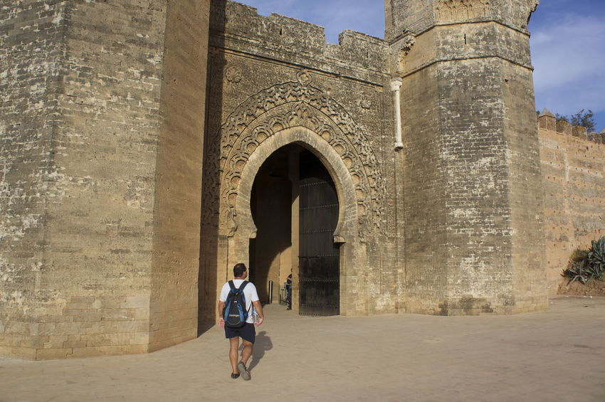 Arch Architecture Building Exterior Built Structure Casual Clothing Chella ChellaH Day Full Length History Leisure Activity Lifestyles Men Person Rabat Rear View Sky Standing Stone Wall Tourism Tourist Tourist Walking