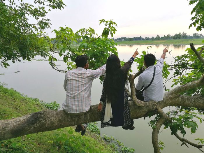 Enjoy The New Normal Rear View Togetherness Adult Water People Sky Outdoors Bonding Human Body Part Friendship Women Men Nature Young Adult Day Tree Leisure Activity Pointing Pointing Far Three People Family Sitting On A Tree Relaxing On The Edge