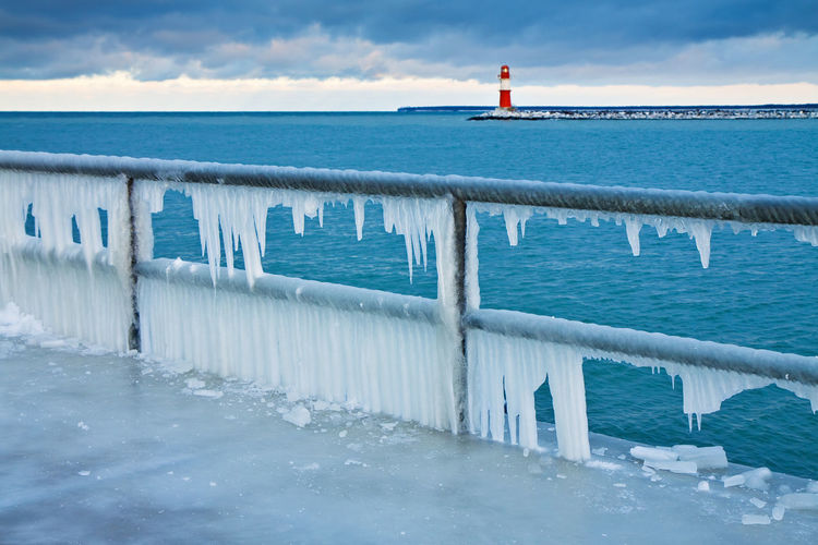 Icicles on railing with lighthouse in background