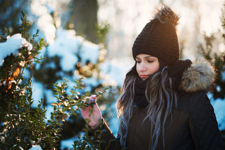 Young woman holding plant during winter