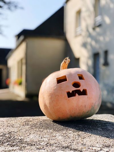 Close-up of jack o lantern on road against building