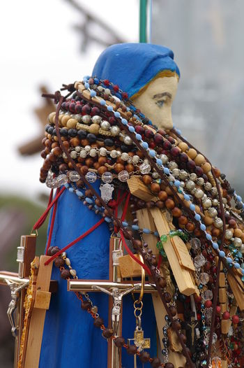 Low angle view of multi colored rosary beads on jesus christ