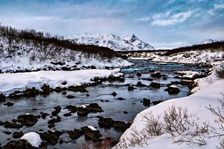 Scenic view of frozen river against snowcapped mountains during winter