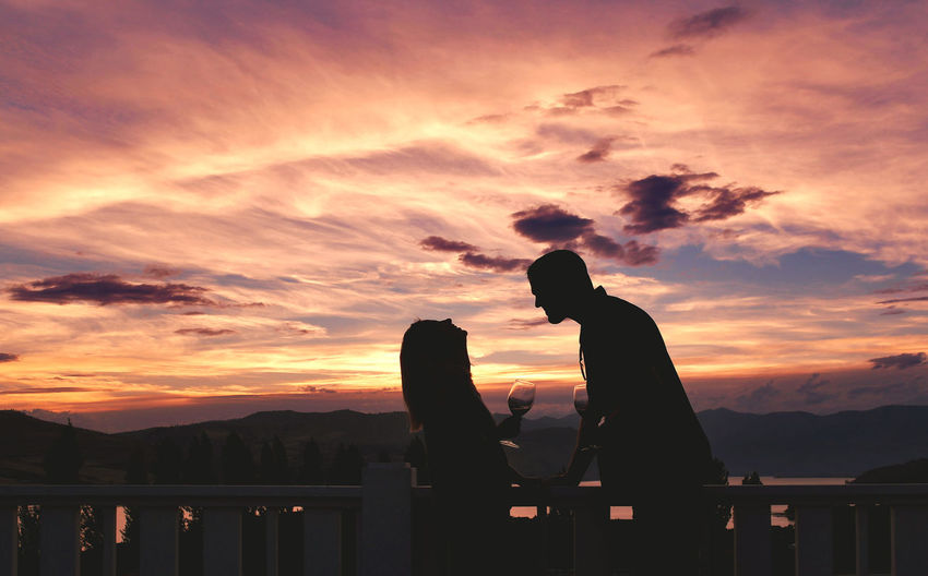Couple sitting standing by railing against sky during sunset