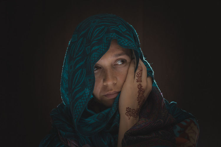 Portrait of young woman against black background