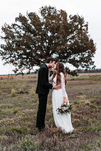 Newlywed couple kissing while standing on grassy land