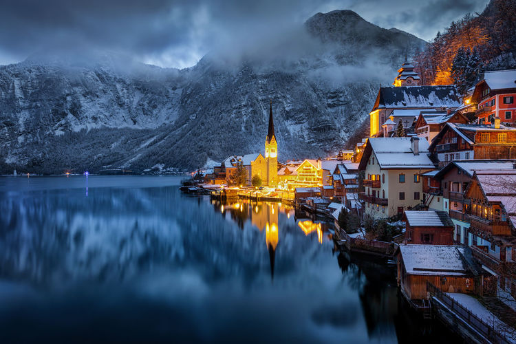 Panoramic view of illuminated buildings by lake against sky during winter