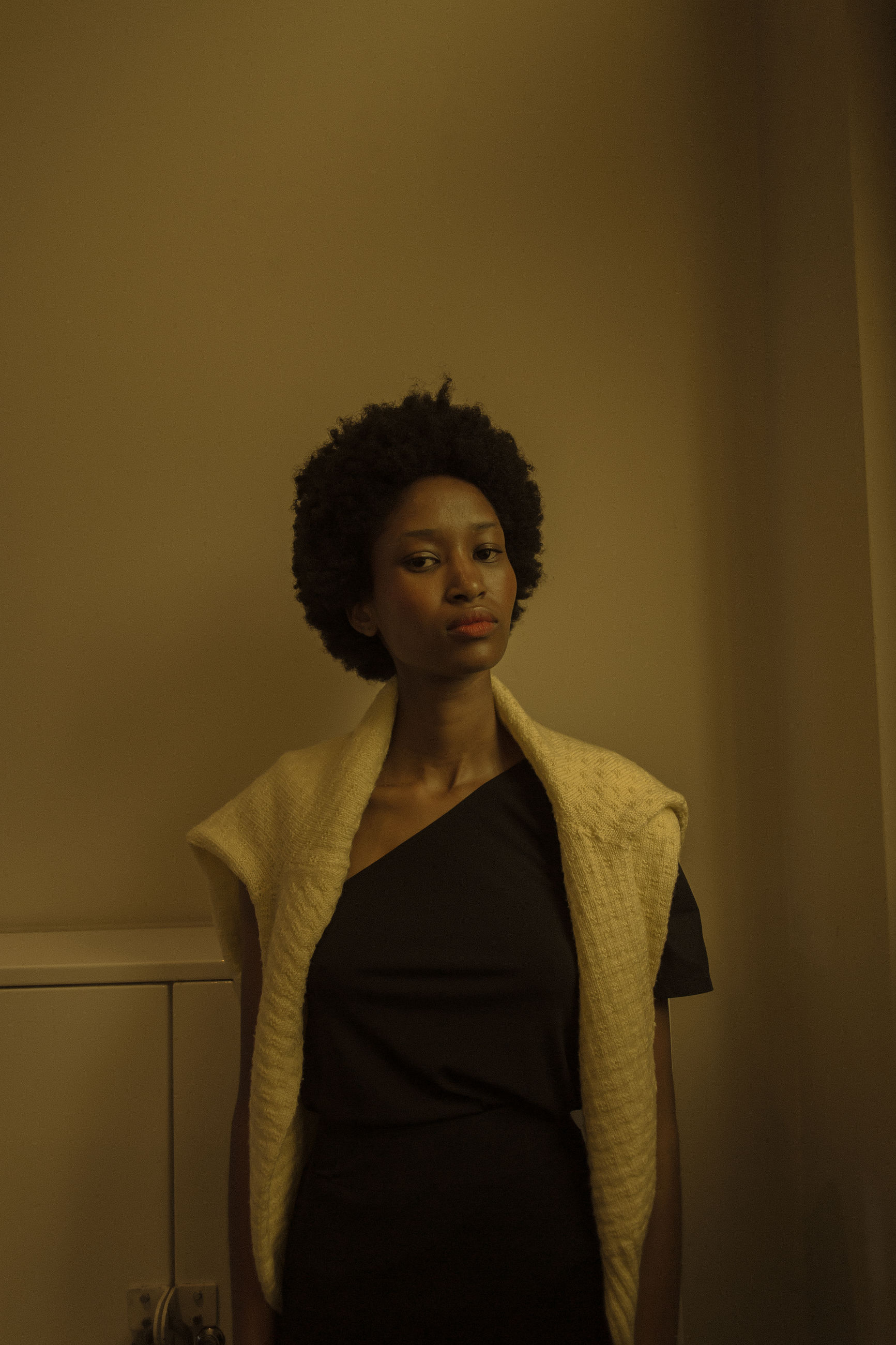 one person, adult, curly hair, indoors, portrait, fashion, women, standing, young adult, hairstyle, looking at camera, front view, yellow, black, waist up, businesswoman, person, clothing, serious, female, business, brown hair, human hair, looking, copy space, elegance, individuality, three quarter length