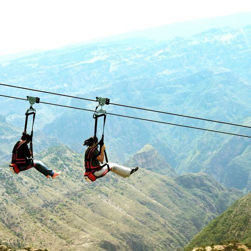 Women On Zip Line Over Mountains