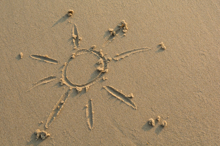 Sun drawn in sand, close up Beach Sand Sunlight Wet Holiday Vacations Backgrounds Summer Summertime Fun Happy Happiness Design Handwriting  Sketching Draw Drawing Abstract Copy Space Coast Outdoors Sea Playing Joy Sunny
