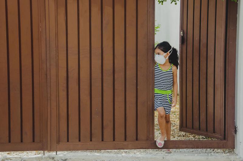 Full length of girl wearing mask standing at entrance