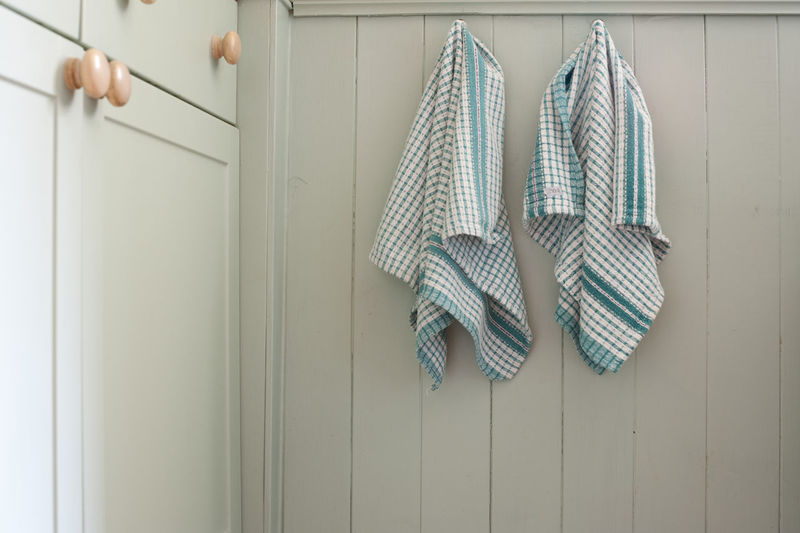 Dish towels hanging on wooden wall in kitchen at home